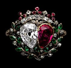 Gold and silver ring set with diamonds and colored stones. The bezel is in the form of pear-shaped ruby and diamond double heart, framed within an emerald and ruby wreath of myrtle leaves and berries, surmounted by a viscount's crown, the strawberry leaves set with rubies, the points between with rose diamonds. Narrow hoop. Mid 18th century.