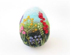 Needle felted egg made from pure roving wool one single barbed needle and lots of love. Walking in a wildflower meadow is a sure sign of spring and summer . . . this needle felted egg mini landscape focuses on the bee and butterfly attracting flowers such as Hollyhock,Lavender,Primrose,Poppy,..,etc. With vivid colors, intricate details,the colours are soft and dreamy,with a mixture of textures. I use a variety of wool fibers to needle felt the background landscape. measurement: height ~ 3,5…