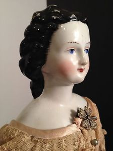 "Rare-Antique-China-Head-Doll-Circa-1860-Elaborate-hair-and-gown. stunning antique china head doll.  She is 19"", with elaborate black hair that has minor rubbing in the back.  She wears her original flowing gown.  Her lower arms and legs are china as well with molded/painted black boots. Ebay, 11/14, asking $3,000."
