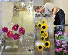 A worker checks on flowers embedded in ice at Arakawa Himuro in Kyoto's Higashiyama Ward.