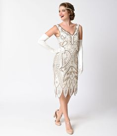 We cant look away, darling! Unmistakably commanding, the Malvina Flapper Dress from Unique Vintage is a striking silhouette! The sleeveless, V neck ivory design is intricately hand beaded in a gorgeous boteh pattern of blooms and bursts of antique gold b