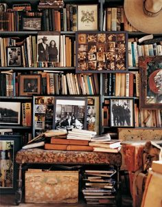 LOVE this stacked book shelf; cluttered but so chic and vintage in its charm! And the old photographs dotted around are so interesting!