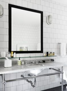 Sleek bathroom design with white square porcelain tile backsplash with gray grout paired with black tile floor.