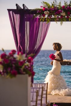 This purple beach wedding arch is gorgeous!! Those pink and white flower arrangements are perfect!