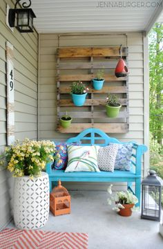This porch isn't afraid of experimenting with color! Brightly painted pots hung on a repurposed shipping pallet add to its cheery mood.