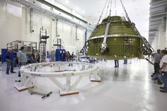 Orion crew module hoisted in air and moving toward round test stand on floor at left