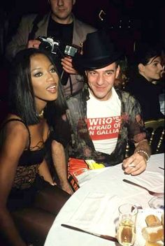 Naomi Campbell and John Galliano.   From the late 1970s through the 1990s, Les Bains Douches was a nightclub in Paris located at 7 rue du Bourg l'Abbé in the 3rd  arrondissement. What made it distinctive from most other nightclubs were the availability—as the club's very name promised—of large baths for its patrons to cool off or generally frolic in. photographer Foc Kan