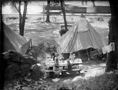 Camping at Devil's Lake State Park; 1919. The Herman Taylor family camping at Devil's Lake. There is a moving train in the background. Baraboo, WI | Wisconsin Historical Society