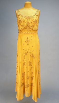 "Evening Gown: ca. 1929, beaded georgette, bias-cut skirt, allover crystal bead and rhinestone decoration, crepe de chine under-dress.    Label: ""Maria La Tour 29 West 57th Street New York"""