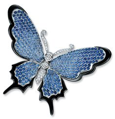 Butterfly wings in blue sapphire pavé graduating in color, are edged with black onyx, in 18-karat white gold. Moveable wings are spring-mounted to the diamond body, so the wings can flutter.