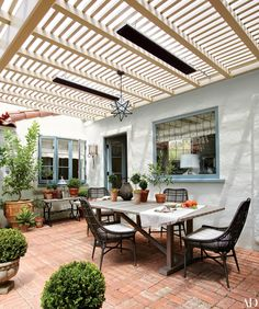 The terrace of designer Madeline Stuart's Santa Barbara, California, getaway serves as an alfresco dining room, featuring a teak table by Janus et Cie and Palecek chairs; the star pendant light is by Reborn Antiques.