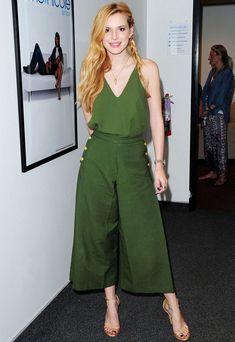 Bella Thorne usa macacão verde e sandália dourada para evento.