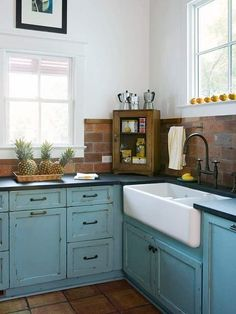 Country kitchen sink, and turquoise cabinets w/ dark countertops.