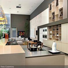 Die elegant wirkende Wohnküche mit klaren Ecken und Kanten wird durch große, runde Hängeleuchten aufgelockert und gewinnt durch sie einen verspielten Charakter.…