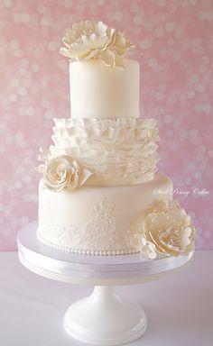 Wedding cake with ruffles, roses, peonies, hydrangeas, & lace.