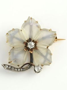 Vintage carved camphor glass flower brooch with diamonds, circa 1920. The brooch is set in 18 karat white gold and sterling silver with carved camphor glass petals with a 0.15 carat Old Mine cut diamond and rose cut diamonds at 0.10 carat total weight.