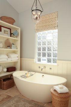 briques de verre, baignoire autoportante, étagère blanche et plafonnier rustique