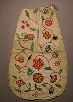 Early 1700's. This pocket consists of two unbound and unlined fronts of twill weave linen, partially sewn together, one incomplete. Both are embroidered in chain stitch with flowers, stems and leaves in coloured wool. There are no ties. It is not known why these pocket fronts are assembled in this unusual way.  Salisbury and South Wiltshire Museum.SBYWM.61.56