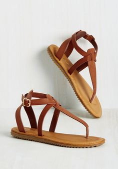 A long search for the perfect place to pitch a tent ends with a lush clearing and swapping your boots for these caramel sandals. Clad in the intersecting T-straps and gold buckles of this treaded pair, you embrace the tickle of soft grass on your feet and the soothing tranquility of nature.