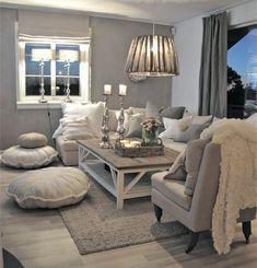 Living en tonos grises, textil en gris y blanco. Candelabros en la mesa de centro y pufs blancos a un costado del sofá