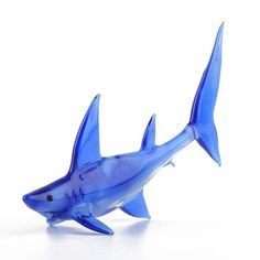 """""""Beautiful Blue #Shark Glass Art Item No. GF00039A01 $15.39 About 5 1/2"""" long blue shark was Hand-blown by a Russian glassblower with care and small details. The semi-transparent blue color looks lovely in all varieties of lighting. This blue shark is a Requiem shark, part of the Carcharhinidae family. A unique gift for the sea lover! Because each figurine is crafted by hand, colors may vary and no two are exactly alike. #sharkweek Blue Shark, Blown Glass Art, Glass Figurines, Glass Animals, Royal Doulton, Glass Design, Unique Gifts, Semi Transparent, Beautiful"""