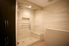 New, clean bathroom we installed in a modern condo. The glass doors, bench seat and built-in box shelf make the space!