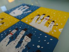 Canvas art: handprint snowman family on one square, footprint Rudolph on another, handprint Santa on a third, and handprint wreath on the last with family name and year