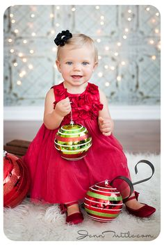 #IDEA FOR BABY CHRISTMAS PHOTO PORTRAIT - use white lights for a backdrop , some nice big christmas decorations and just looks this pretty lady-in a lovely red dress with accessories
