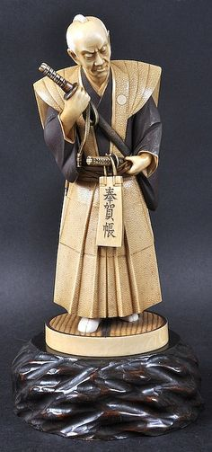 A FINE EARLY 20TH CENTURY JAPANESE MEIJI PERIOD IVORY OKIMONO modelled as a samurai holding a scroll. Signed. Ivory 8.25ins high.