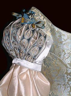 slashed sleeves with piped edging and blue-gold ribbon decoration
