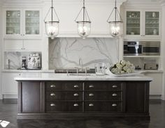 Statuary marble, furniture like island in dark wood, and white perimeter cabinets. The pendants add a casual element.