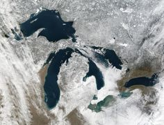 The deep blue and green waters of the Great Lakes stand out against the snow-covered landscape of the northern United States and southern Canada in this true-color Moderate Resolution Imaging Spectroradiometer (MODIS) image. Lake Superior is in the far north, with Lakes Michigan (west) and Huron (east) arcing toward its southeastern tip. South of Huron, Lake Erie's waters swirl with dense clouds of tan sediment, while Lake Ontario remains clear. Taken December 26, 2003, by the Terra satellit...