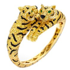 Cartier, a one of a kind Double Headed Tiger bangle bracelet, mounted in 18k yellow gold, pavé-set to the front with circular-cut fancy yellow diamonds, 280 calibré black onyx designed as stripes, 2 pear-shaped emerald eyes and black onyx nose, with pivoting heads. 977 diamonds weighing a total of approximately 15.09 carats. Signed Cartier, numbered 607986.