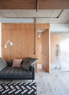 Distribuição. Uma divisória de carvalho americano divide o estar e o closet, que recebeu ainda painel de vidro pontilhado. Os armários são fechados (Foto: Gui Morelli / Divulgação)