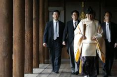 Japan's Prime Minister Shinzo Abe (2nd L) is led by a Shinto priest as he visits Yasukuni shrine in Tokyo December 26, 2013. Abe visited Tok...
