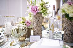 """I'm kind of obsessed with this Rustic Beach Theme DIY centerpiece.  The flower vase is made out of an empty pringles box and rocks!  How cool is that?  And the table number doubles as a """"message in a bottle"""" with a love poem inside of it.  Soooo unique!"""