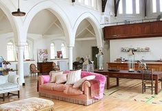 The first church turned into a home is noticeably modern with pink accents and contemporary furniture. Most old churches have impressive ceilingheight and this building does not disappoint. After renovations the entire church is bright and airy featuring a fantastic and open living room.