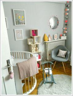 Chambre bébé adorable, chaque détail est pensé. Les couleurs douces en camaïeu bleu-vert + guirlande tonique, le fauteuil, les petites boîtes au mur, le miroir, le tapis rond... #nursery #pastel colours