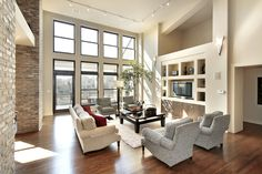 Light colored family room with elevated ceiling, large framed windows, brick walls, wood floor and white rug