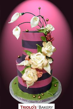 This simple two tiered wedding cake is covered in a sleek stripe design made from modeling chocolate, and adorned with a beautiful cascade of 100% edible modeling chocolate flowers.