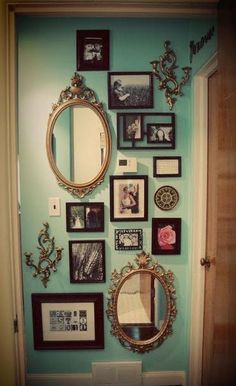 Vintage mirrors and pictures on a turquoise wall.