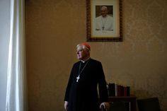 Schwarzes Gewand, weißes Gewand: Kardinal Müller vor einem Bild von Papst Franziskus