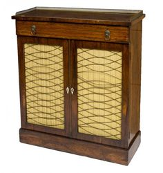 AN EARLY 19TH CENTURY ROSEWOOD SIDE CABINET, with three quarter pierced brass gallery and a frieze drawer, above two brass trellis pattern doors, raised on plinth base, 35.5in (90cm)h x 35in (89cm).
