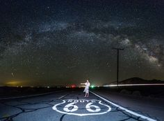 Stargazing night shot of hitch-hiker on Route 66.