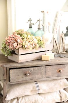 French farmhouse guest toom table, dresser, pillows, flower crate, soaps, accessories, decor