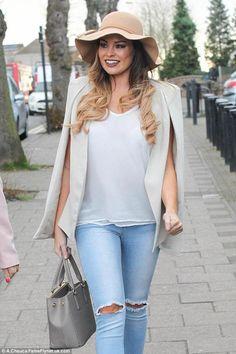 Ombrelette smiling in tan hat w/ sinusoidal brim carrying concrete handbag