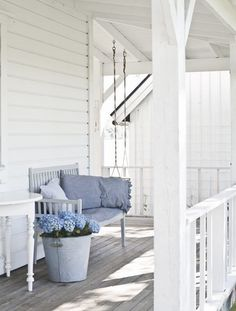 I have a white porch, but it never looks like this...time to jeuge with some throw pillows and a proper side table