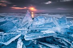 The sun pierces the clouds and sets aglow the ice shards piled up on the shore of the Lake Superior, USA.