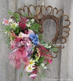 Victorian Garden Heart Wreath. A sweet floral bouquet in lovely shades of raspberry pink, cornflower blue, soft lilac and ivory rest upon lush greenery, gracing the edge of a decorative grapevine hear