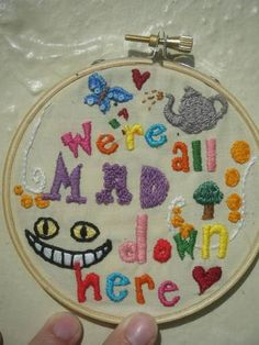 I think it should say We're All Mad here.  I would love it have a white/red rose, a heart, a top hat, the cheshire grin, and a tea pot & cup